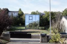 La maison se démarque dans un contexte suburbain.