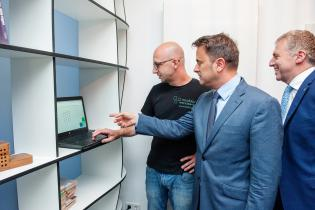 Kai Hengen, ici aux côtés de Xavier Bettel et Tom Oberweis, montre le site Form.bar, avec lequel sa menuiserie a un partenariat.