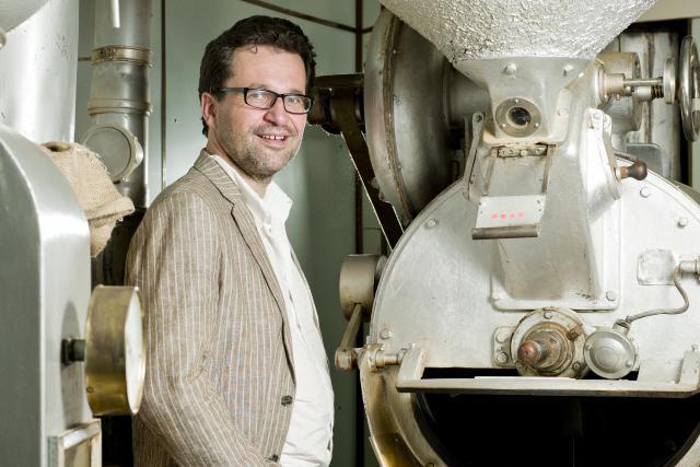 Jean-Louis Zeien, président de Fairtrade Lëtzebuerg, pose devant un machine à torréfier le café issu du commerce équitable, en vogue au Luxembourg.